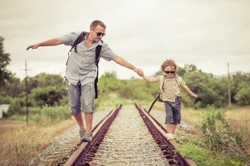 father-son-walking-railway-track